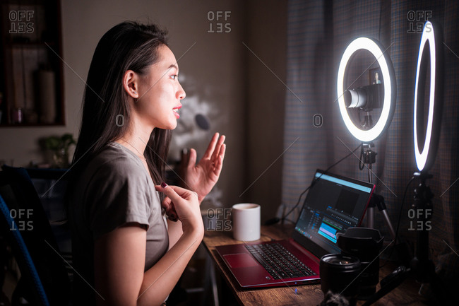 Young Asian female beauty influencer with bright makeup waving hand and talking with subscribers while sitting at table with gadgets and ring light and filming video on camera