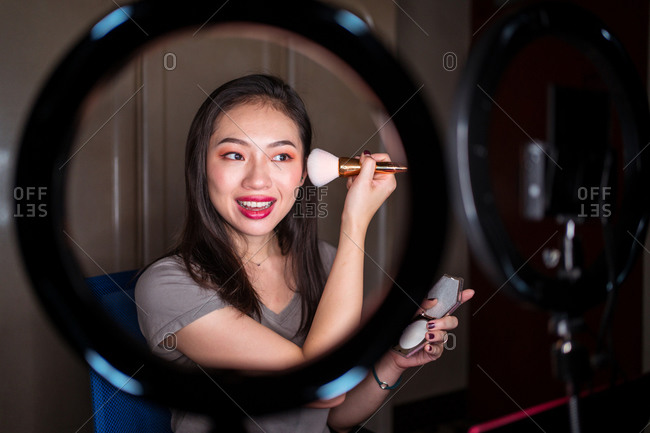 Young Asian woman in casual wear holding mirror and recording video tutorial for beauty blog at home workplace with ring light and camera