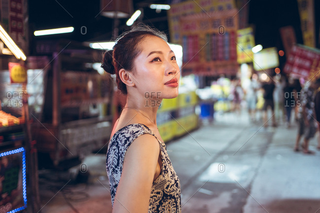 Side view of confident ethnic female standing on crowded street in Night Market in Taiwan and looking away
