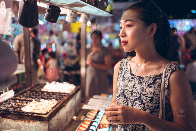 Side view of female in summer dress standing near counter on crowded street in Night Market in Taiwan