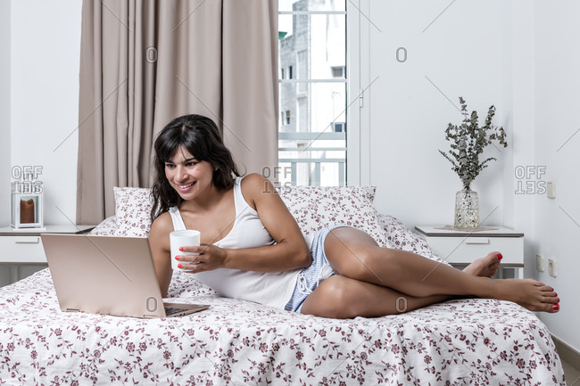 Cheerful female in pajama lying on soft bed and watching interesting movie while enjoying hot beverage in a mug in the morning and relaxing at home
