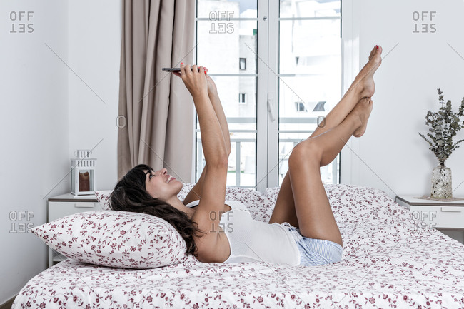 Side view of charming female in sleepwear resting on bed with raised legs and taking photo on smartphone camera