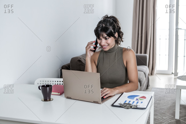 Young smiley female using mobile phone with touchscreen while sitting at desk with papers and working on laptop with black screen