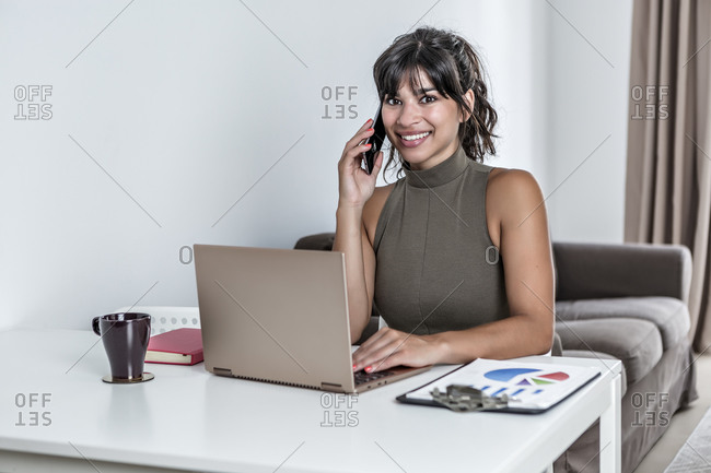 Young smiley female looking at camera using mobile phone with touchscreen while sitting at desk with papers and working on laptop with black screen