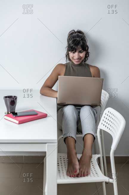 Full body optimistic female in casual wear sitting on chairs near desk and working on contemporary netbook from home
