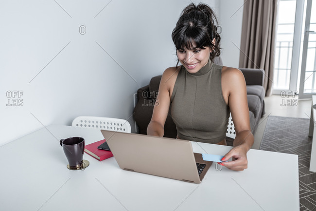 Smiling female working on the computer and paying for purchases with credit card in modern apartment