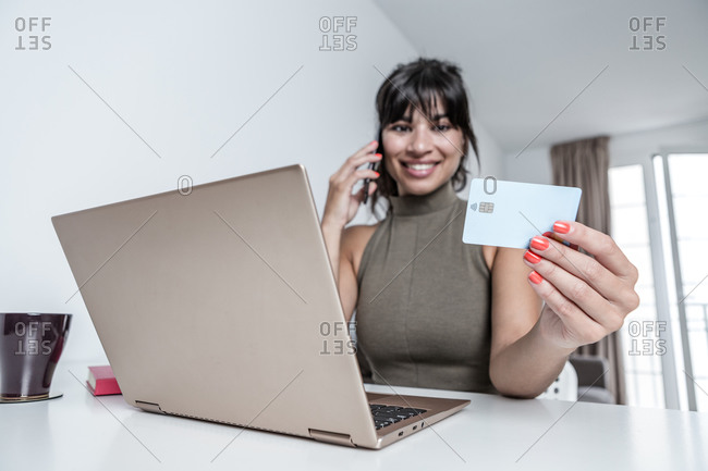 Smiling female having phone conversation while working on laptop and paying for purchases with credit card in modern apartment