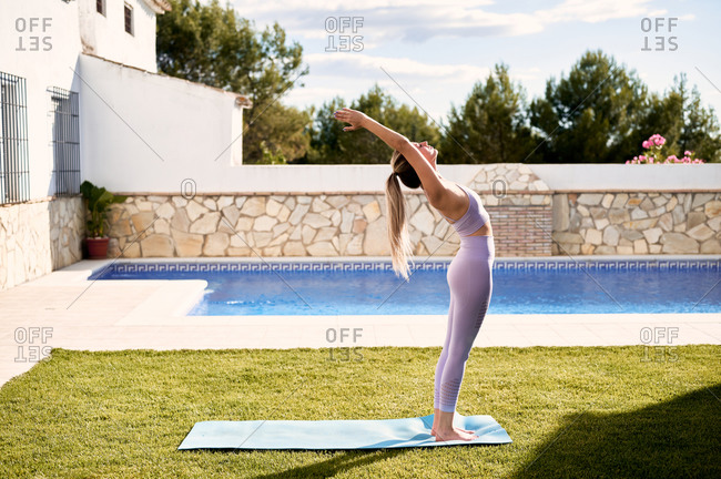 Side view of slim female wearing sports bra and leggings standing on mat near pool and practicing yoga in Urdhva Hastasana