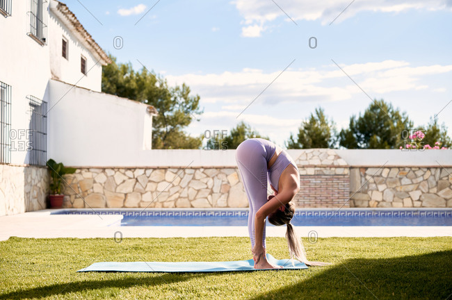 Side view of flexible female in sportswear standing and performing forward bend while practicing yoga on mat on lawn