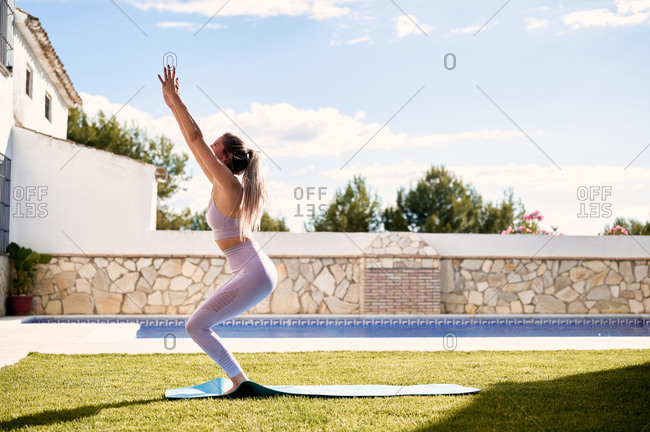 Anonymous female in active wear standing barefoot on mat in courtyard and practicing yoga in Utkatasana on sunny day