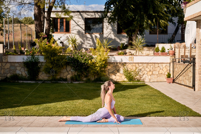 Side view of serene female sitting on mat in Ardha Kapotasana at poolside and meditating with closed eyes while practicing yoga in backyard in summer
