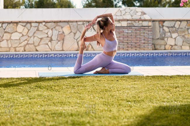 Side view of tranquil female in active wear sitting on mat in Eka Pada Rajakapotasana and practicing yoga in courtyard near poolside