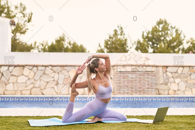 Side view of tranquil female in active wear sitting on mat in Eka Pada Rajakapotasana and practicing yoga in courtyard doing classes online on laptop