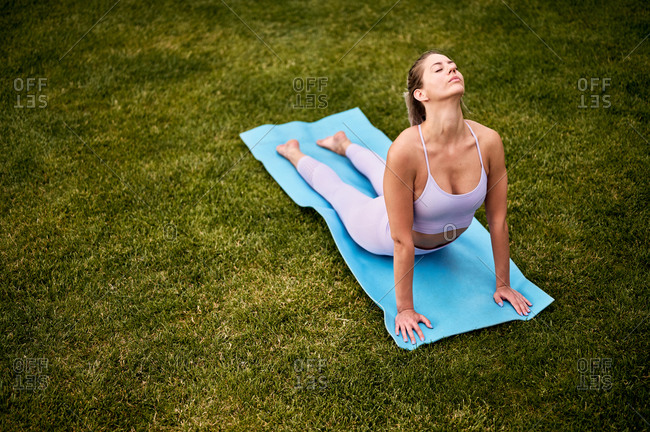 From above side view of peaceful female practicing yoga on mat in Bhujangasana with closed eyes on lawn in backyard