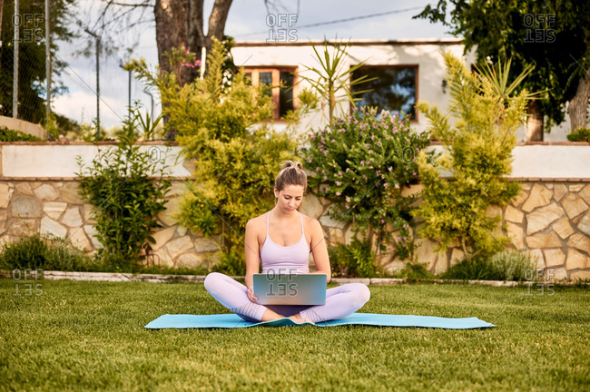 Calm female in sportswear sitting barefoot on mat and choosing online tutorial for practicing yoga