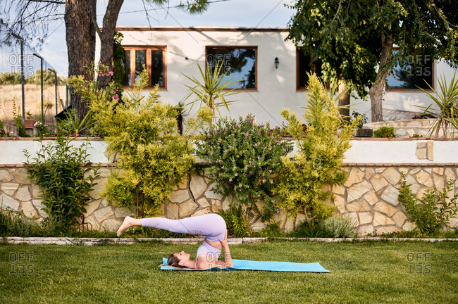 Side view of flexible female in active wear practicing yoga in Halasana with closed eyes on mat in backyard