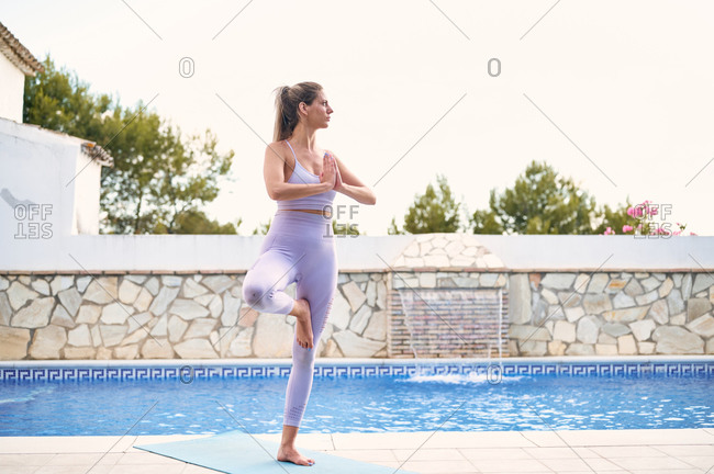 Tranquil female in sports leggings and bra balancing on leg in Vrksasana with Namaste gesture while doing yoga and looking away