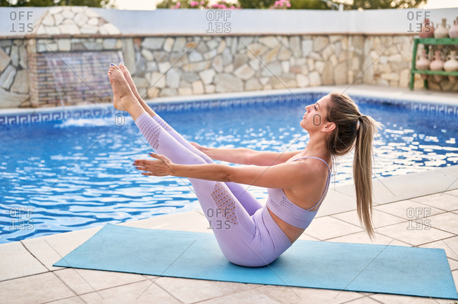 Side view of concentrated female in active wear practicing yoga in Navasana at poolside in courtyard in summer