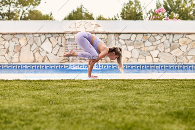 Side view of focused female in active wear balancing on mat in Bakasana and practicing yoga at poolside in summer