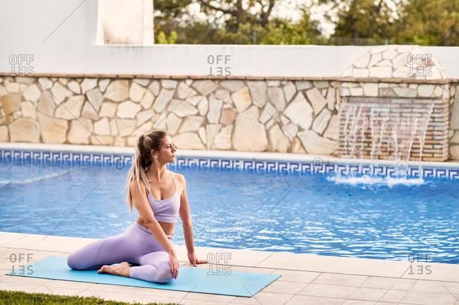 Young fit barefoot female in sports clothes doing Seated Twist on yoga mat and looking away near swimming pool with rippled water near stone wall in daylight