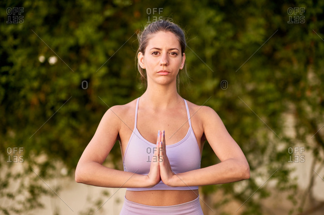 Tranquil female in sports leggings and bra with Namaste hands gesture while doing yoga and looking at camera