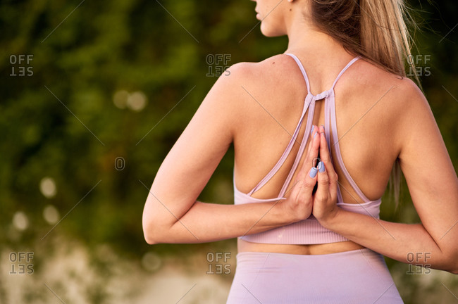 Unrecognizable crop woman in sportswear practicing yoga with Namaste gesture behind back and looking away