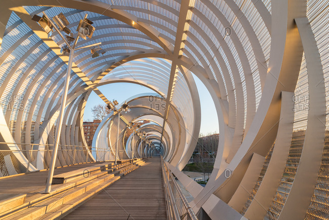 Perspective inside passage of helical cone shaped Arganzuela bridge with internal metal intertwined spirals crossing diagonally in sunset time in Madrid