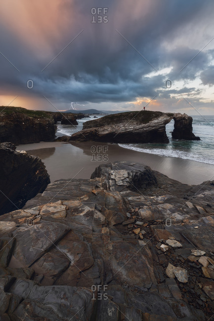 Rough rocks on shore of calm ocean under grey clouds on bright sky
