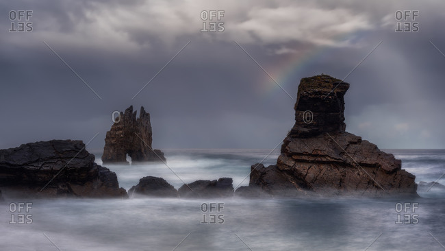 Calm surface of ocean and stones under thick fog with bright rainbow in cloudy sky