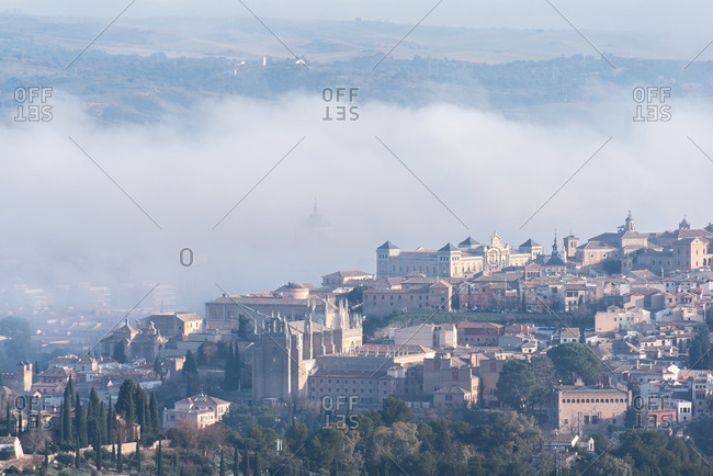Amazing cityscape with aged stone buildings located on hill on background of cloudy foggy sky