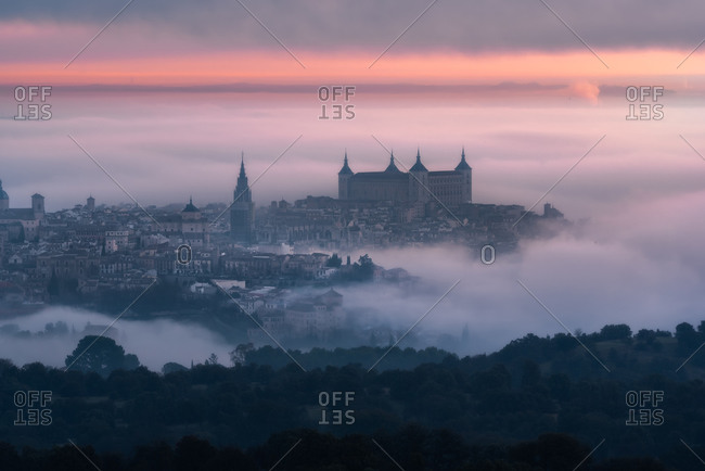 From above wonderful landscape of medieval castle built over city in misty colorful sunrise