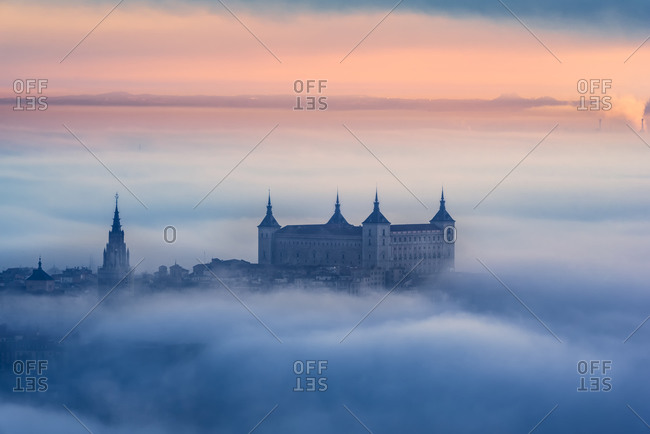 From above wonderful landscape of medieval castle built over city in misty colorful sunset