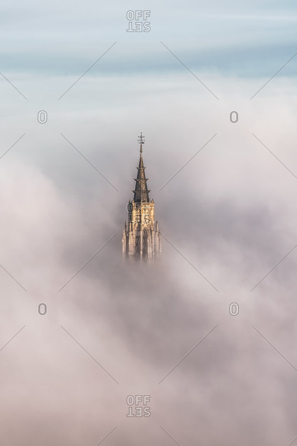 Picturesque view of peak of ancient castle surrounded by thick gray clouds under sky in Toledo