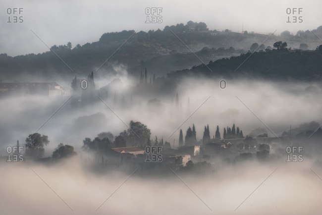 Drone view of mystery landscape with hills covered with trees located in countryside in foggy day in Toledo