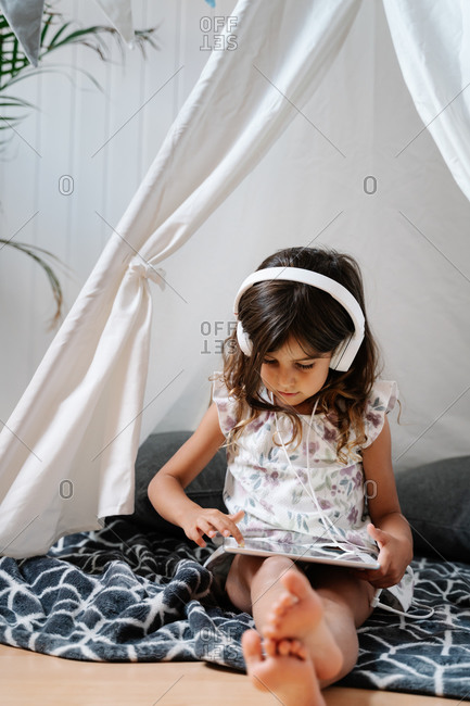 Full length concentrated barefoot female child in casual clothes sitting on blanket on wooden floor and using tablet and headphones in home tent