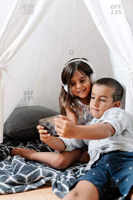 Cheerful little girl with long hair in casual dress and headphones sitting on blanket with boy showing screen of smartphone in homemade tent in daylight