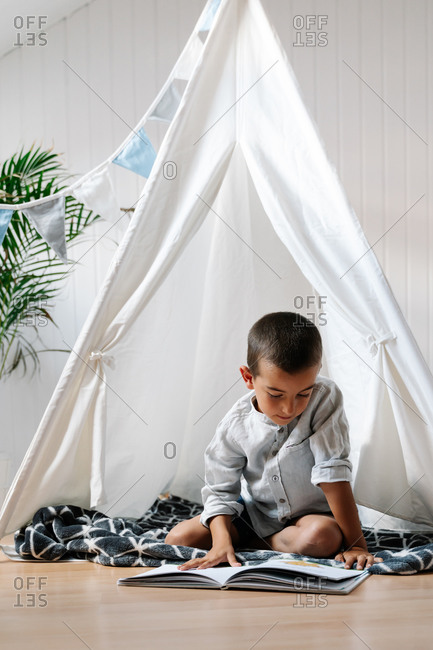 Full body little boy sitting on blanket on wooden floor while reading book in homemade tent decorated with garland of flags in apartment in daylight