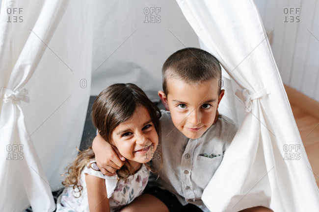 From above of positive little boy in casual clothes hugging smiley sister in dress while sitting together in cozy children tent in room in daylight