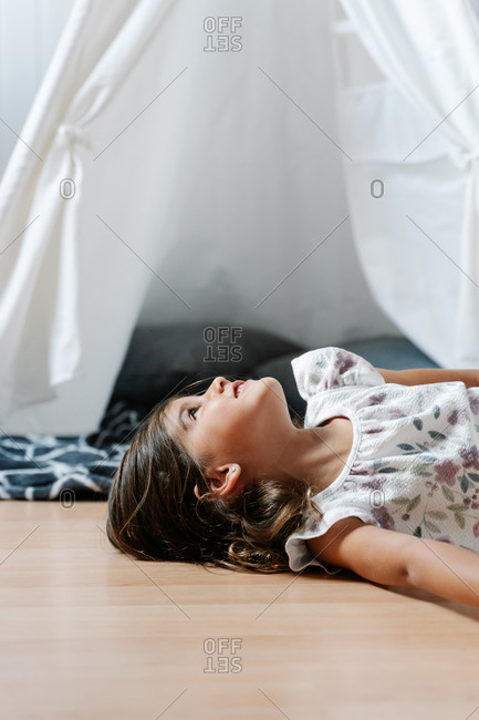 Side view of female kid in casual clothes lying on wooden floor alone against children tent with blanket and pillows and looking up in light room of apartment