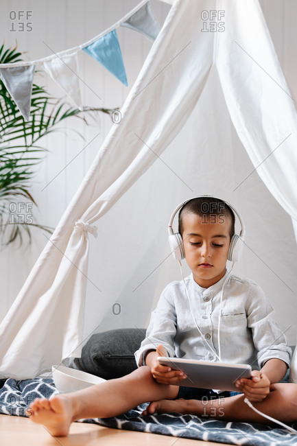 Full length concentrated barefoot male child in casual clothes sitting on blanket on wooden floor and using tablet and headphones in home tent