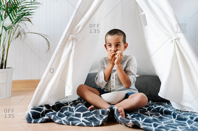 Little boy eating snack from bowl while sitting on blanket in cozy home tent in light room near plant