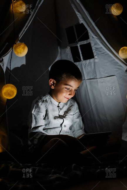 Full length happy boy in casual clothes sitting on blanket watching video on tablet in homemade tent decorated with garland with big lights in moon shapes in darn room at night