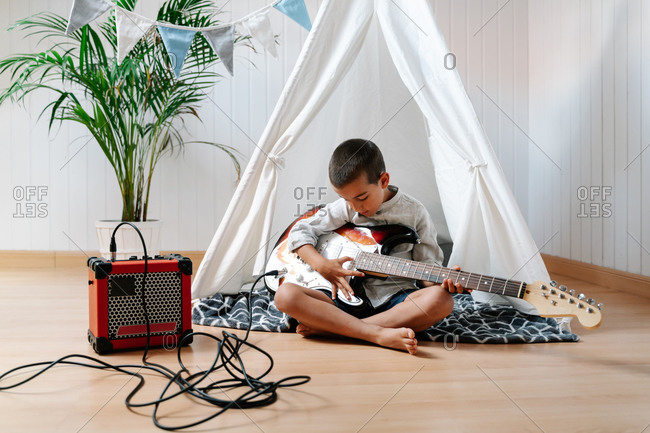 Full body concentrated barefoot little boy in casual clothes sitting on blanket and trying to play guitar connected with combo amplifier on wooden floor in tent