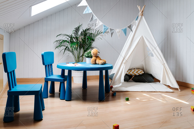 Cozy white tent with cushions and flags placed with blue chairs and table in light playroom decorated with green plants in modern apartment
