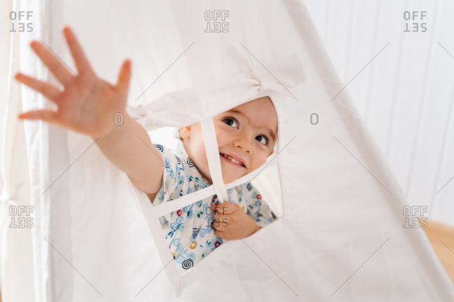 Cheerful little boy in colorful shirt outstretching arm through window of white tent while playing in light nursery at home