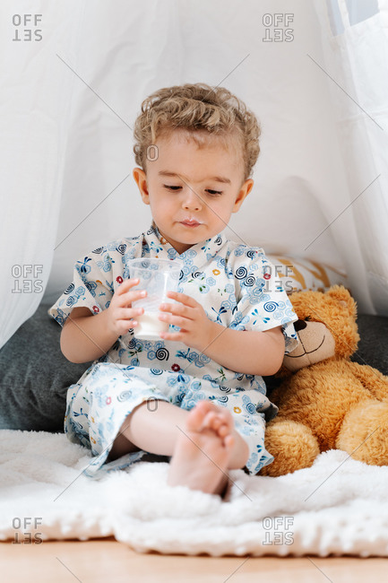 Adorable curly haired preschool boy in colorful clothes drinking milk from plastic cup while sitting with teddy bear under cozy white tent in playroom at home