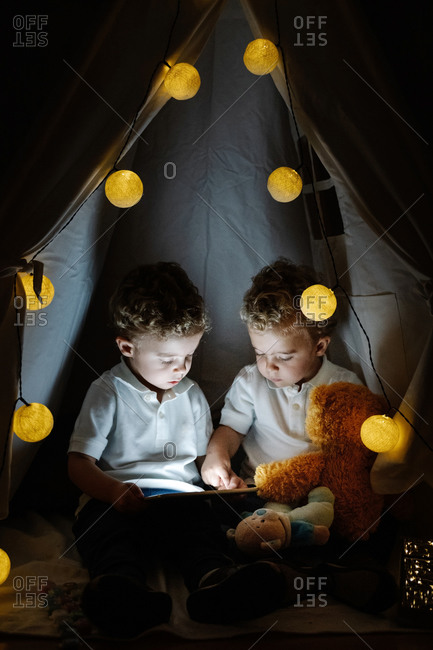 Cute little twin boys with curly hair sitting inside cozy tent with light garland and playing with tablet while spending time together in cozy playroom at home