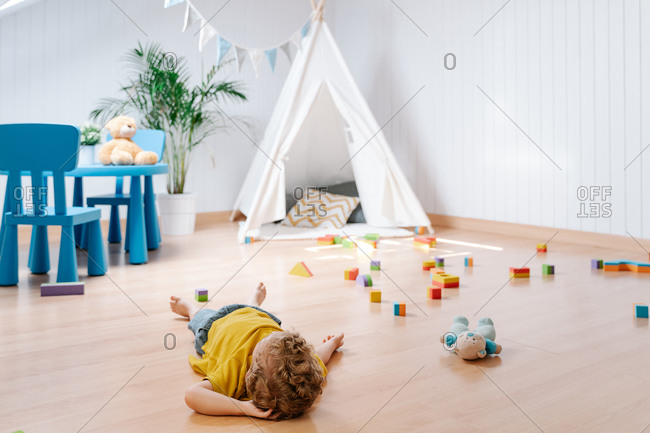High angle of unrecognizable little boy with curly hair lying on parquet floor near toys while resting after playing in cozy playroom with tent