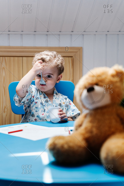 Cute curly haired little boy sitting at table with teddy bear and eating yummy yogurt while resting after playing in modern nursery at home