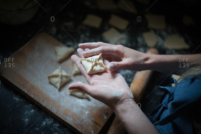 From above of crop anonymous woman preparing similar square dumplings with decoration on top above cutting board with flour near wooden rolling pin